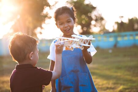 Two asian child girl and boy playing with toy wooden airplane in the park together at sunset time with fun