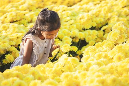 Cute asian child girl love flower and having fun with beautiful flower in the flower garden