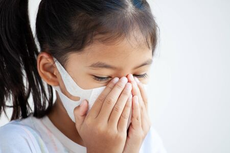 Cute asian child girl wearing protection mask to against air smog pollution with PM 2.5, anti smog and viruses. Air pollution and environmental concept.
