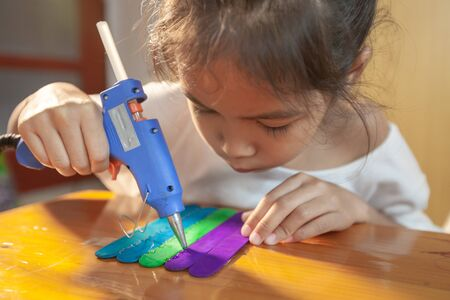 Asian child girl glueing colored ice cream sticks by hot melt electrical glue gun. Children have fun to make house on a handicraft project. Banque d'images