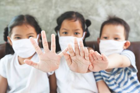 Asian children boy and girls wearing protection mask and show stop hands gesture for stop corona virus outbreak. They stay at home quarantine from the coronavirus Covid-19 and air pollution pm2.5. 写真素材