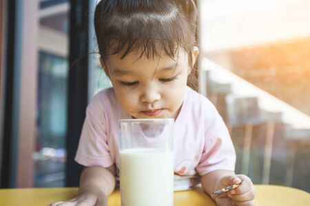 Cute asian little child girl drinking milk and eating snack in breakfast time