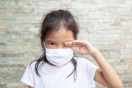 Asian child girl wearing protection mask and rubbing her eyes. She stay at home quarantine from the coronavirus Covid-19 and air pollution pm2.5. Air pollution and Medical concept.