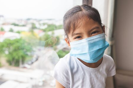 Asian child girl wearing protection mask and stay at home quarantine from the coronavirus Covid-19 and air pollution pm2.5.