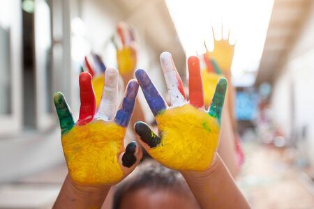 Cute asian child boy and girl with painted hands playing together with fun and happiness