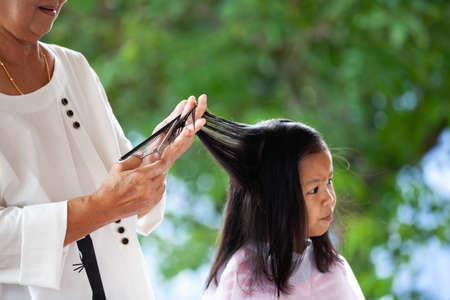 Cute asian child girl getting haircut by grandmother at home