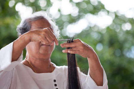 Grandmother making hairstyle to her granddaughter with scissor at home 写真素材