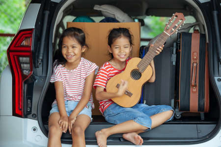 Happy asian child girl playing guitar and singing a song with her sister in a car trunk in family trip. Foto de archivo