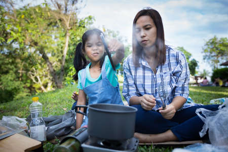 Cute asian child girl having fun to help her mother cooking while camping with family.