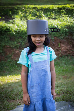 Happy asian child girl put a pot cover on head and having fun to help her parent cooking while family camping.