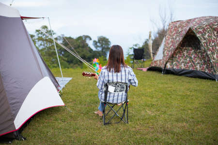 Asian woman sitting on picnic chair and playing guitar while camping with family in the camping site in the beautiful nature. Family enjoy with nature and camping concept.