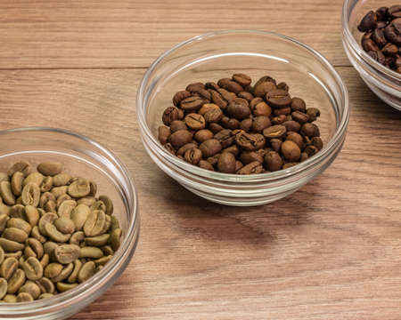 heavily: Coffee beans of medium roast in a glass bowl surrounded by green and heavily roasted 2
