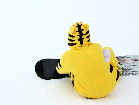 Snowboarder in a yellow tiger suit on the slopes