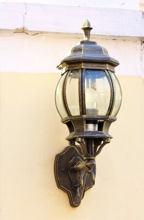 black vintage street lamp  on the white  wall photo