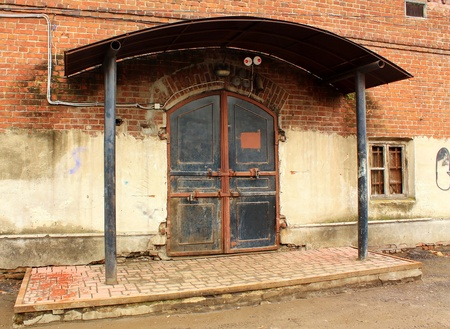 under control: metal door of an old warehouse under control of  alarm system