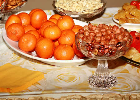 Tangerines and nuts in vases on the table Stock Photo - 13361536