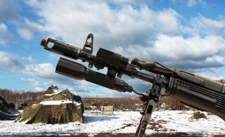 hider: Barrel with flash suppressor, compensator and iron sights against masked military equipment Editorial
