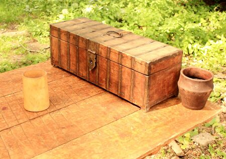 Wooden casket, clay pot and a mug on an old wooden table photo