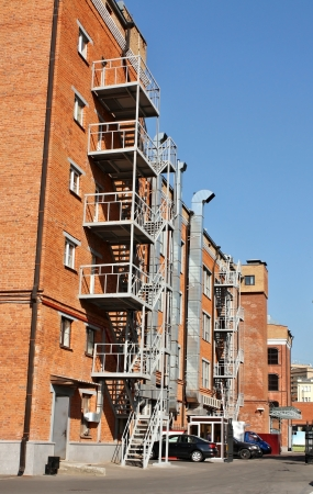 building external: External staircase of the old multi-storey building of red color