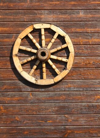 Spoked  wheel of the cart on the wall of the room photo