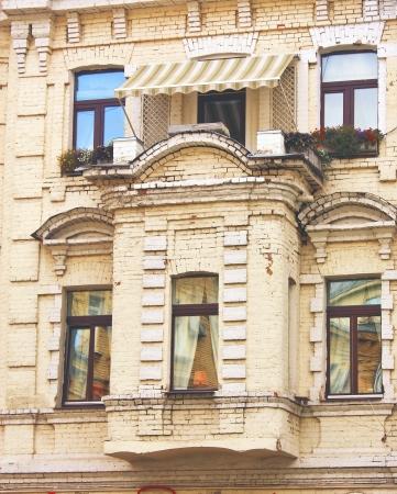 Massive balcony on yellow brick building wall