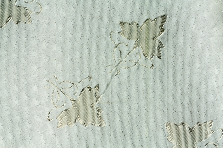 gleams: White fabric with golden gleams and designs depicting flowers Stock Photo