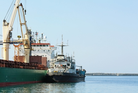 Port berth with material handling equipment and cargo ships at anchor photo