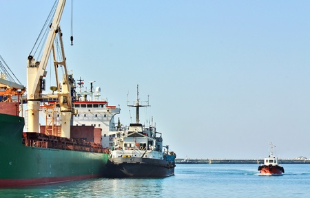 Port berth with material handling equipment and cargo vessel at anchor photo