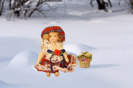 Rag doll - a girl wearing a folklore russian dress sitting on white snow photo