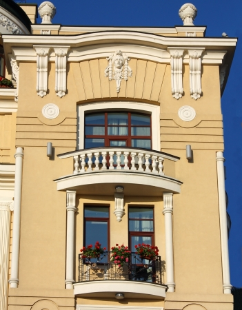 balcony door: Front wall of the house with yellow wall and vintage balconies