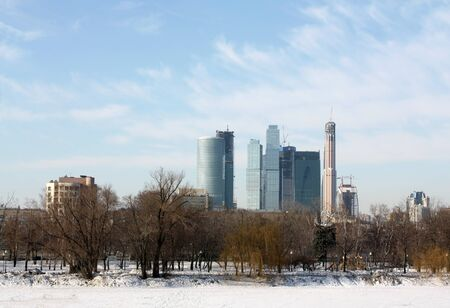 megalopolis: Park with trees in the center of megalopolis on the background of modern buildings Stock Photo