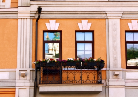 Balcony with a wrought-iron lace fence decorated with flowers photo