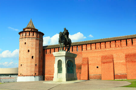 Bronze statue of a medieval Russian warrior in armor on a horse on the background of the fortress wall