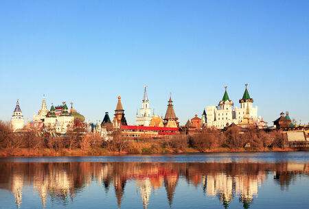 Ancient russian kremlin with colorful towers on the banks of the pond photo