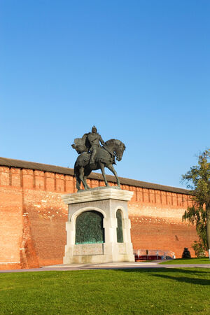 Bronze statue of a medieval Russian warrior in armor on a horse on the background of the fortress wall photo