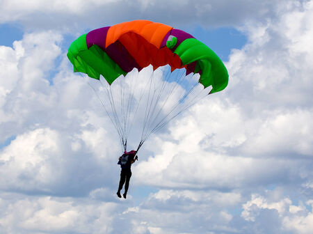 paradglider: Skydiver descends by parachute. Time just before landing.