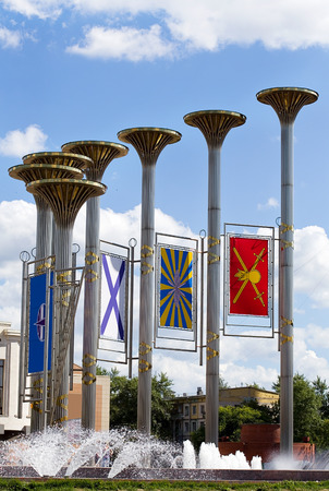 fanfare: Fountain with metal columns in the form of fanfare, decorated with the flags of military symbols