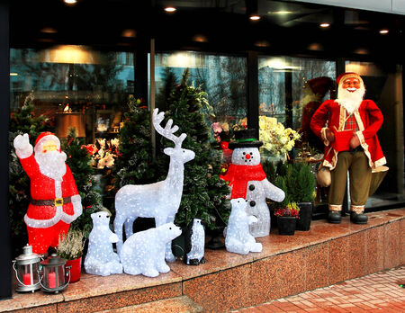 fake christmas tree: Santa Claus, other Christmas characters and a Christmas tree on the sidewalk of the street on the facade of home Stock Photo