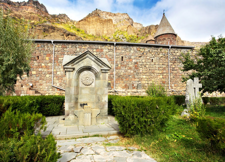 undertaker: Tombstone near monastery wall surrounded by the bush Stock Photo