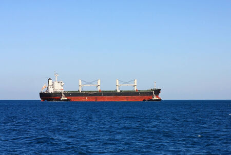 Self-propelled cargo vessel at sea entering the seaport photo