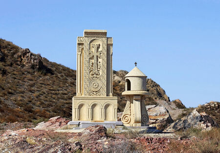 undertaker: Ancient armenian tombstone on the background of a hill and blue sky