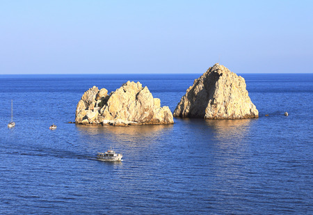 protruding: Two small rocky islands protruding from the surface of the sea Stock Photo
