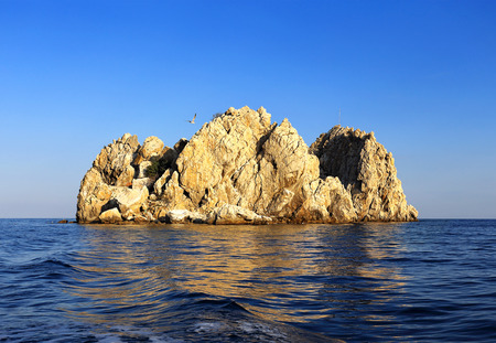protruding: Small rocky island protruding from the surface of the sea