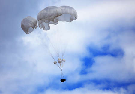 paradglider: Dropping cargo using military parachute system. Time just before landing Stock Photo