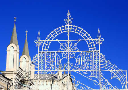 christmas motif: Outdoor Christmas garland on white frame made in the winter motif in the background of church towers Stock Photo