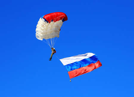 descends: Skydiver descends by parachute with banner of Russa. Time just before landing