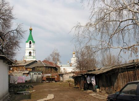 dilapidated: Courtyard with wooden dilapidated house and view of the church