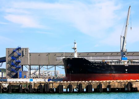 cargo vessel: Port berth with material handling equipment and cargo vessel at anchor Stock Photo