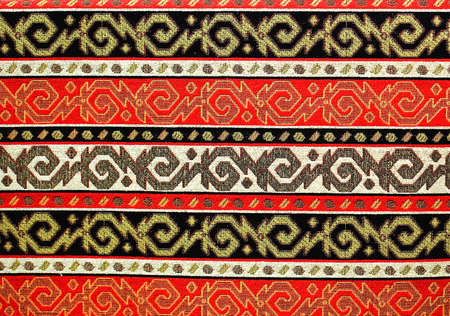 red rug: Colorful fabric with patterns of red, black and gold stitch