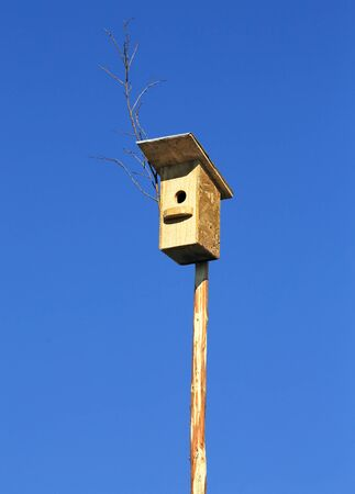 aviary: Birdhouse on a long pole against the blue sky